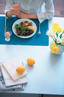 テーブルで朝食をとる女性