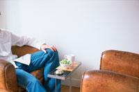 茶色のレザーのソファに座る男性