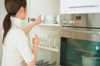 キッチン棚から白い食器を出す女性