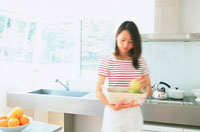 キッチンで果物を持つ女性