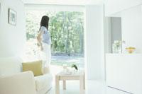 リビングの窓辺に立つ日本人女性