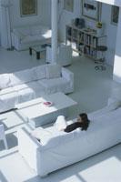白いソファに座る外国人女性の後姿