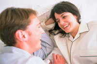 ベッドで微笑むカップル