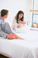 ベッドで語り合うパジャマ姿のカップル