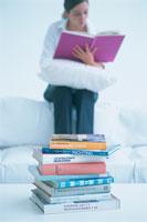 積まれた本と読書する女性