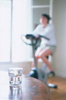 グラス越しにエアロバイクをする女性