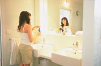 洗面所で鏡に向かう女性 21007005550| 写真素材・ストックフォト・画像・イラスト素材|アマナイメージズ