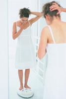 体重計に乗った女性 21007005561| 写真素材・ストックフォト・画像・イラスト素材|アマナイメージズ