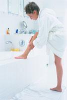 バスルームで足の手入れをする女性