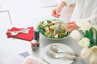 サラダにドレッシングをかける女性の手