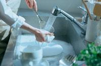 流しで洗い物をする女性