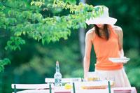 庭でテーブルセッティングする女性