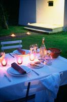 夜の庭のキャンドルのあるテーブル 21007005724| 写真素材・ストックフォト・画像・イラスト素材|アマナイメージズ