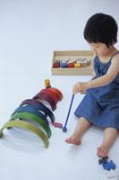 カラフルな木琴で遊ぶ青い服を着た女の子
