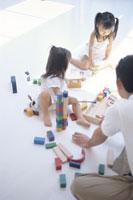 おもちゃで遊ぶ姉妹と父