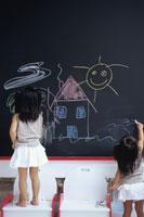 黒板に絵を書く姉妹の後姿