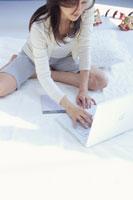 ソファの上でノートパソコンを使う日本人女性
