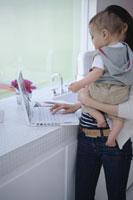 赤ちゃんを抱いてキッチンでパソコンを使う女性