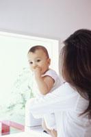 キッチンで赤ちゃんを抱く女性