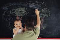 赤ちゃんを抱いて黒板に絵を書く父親