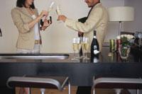 キッチンカウンターでシャンパンをグラスを合わせる男女
