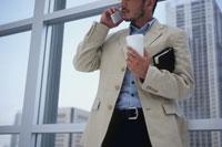 窓辺でドリンクを片手に携帯電話で話す男性