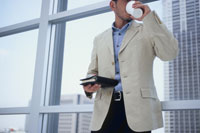窓辺で手帳を持ってドリンクを飲む男性