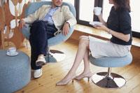 イスに座りエスプレッソを飲みながら話をする男女