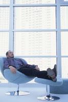 窓辺のイスに座りオットマンに足を乗せた男性