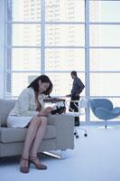ソファに座り手帳を見る女性と窓辺の男性