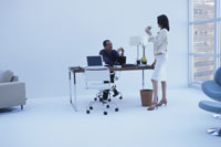 白いオフィスでドリンクを飲む男女