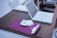 ピンクの封筒や白いノートパソコンのある木目のデスク