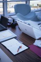 ノートパソコンやスケジュールノートのある木目のデスク