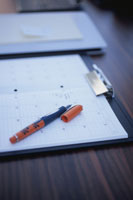 デスクのスケジュールノートの上のペン