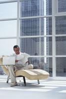 窓辺の寝椅子で書類を見る男性