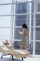 寝椅子のある窓辺で書類を持った女性の後姿