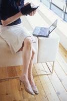 ソファの袖に座り手帳にメモをとる女性