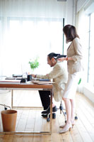 オフィスのデスクに座った男性と傍らに立った女性