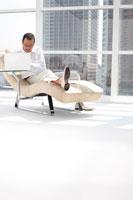 窓辺の寝椅子に座りノートパソコンをする男性