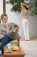 新聞を読む男性と奥に立つ女性