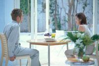 テーブルを挟んで会話するカップル