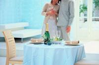 シャンパンのあるテーブルとカップル 21008001703A| 写真素材・ストックフォト・画像・イラスト素材|アマナイメージズ