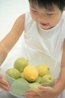 フルーツの入ったガラスボウルを抱く子供