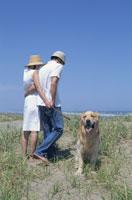 海を眺めるカップルとゴールデンレトリーバー 21014000124| 写真素材・ストックフォト・画像・イラスト素材|アマナイメージズ