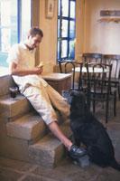 サンドイッチを持った男性と犬