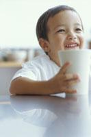 コップを手に微笑む男の子