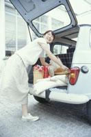 車の荷台から荷物を出す日本人女性