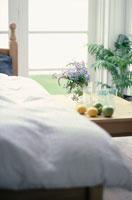 ベッドとテーブルの上に花を生けた花瓶・レモン・グラス