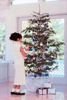 クリスマスツリーに飾りつけをする女の子