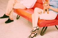 ソファに座るカップルの足元とアビシニアン